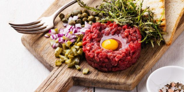 Beef tartare with capers and fresh onion on white wooden
