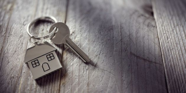 House key on a house shaped keychain resting on wooden floorboards concept for real estate, moving home...