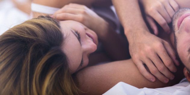 Close-up of happy young woman in bed with