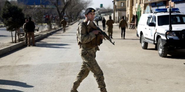 An Afghan security guard inspects the site of a suicide attack at the gate of a Civil Order Police compound,...