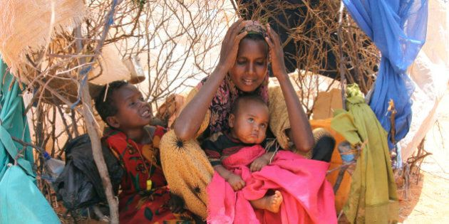 Habiba Osman Ahmed,seated with her two children in a makeshift shelter in Dollow refugee camp in southern...
