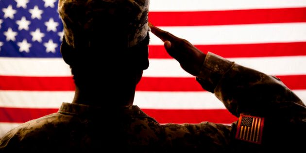 A military veteran salutes her American flag. The patriotic veteran wears a military uniform, and she...