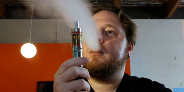 FILE - In this July 16, 2015 file photo, Bruce Schillin, 32, exhales vapor from an e-cigarette in Sacramento,...