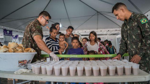 Familias venezolanas hacen fila para recibir comida y bebida en un centro de refugiados de Paracaima...