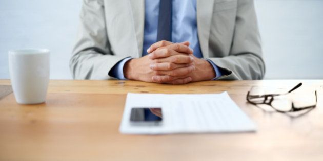 Cropped image of a businessman sitting with hands clasped and paperwork in front of