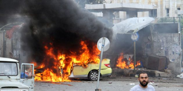 People inspect the damage after explosions hit the Syrian city of Tartous, in this handout picture provided...