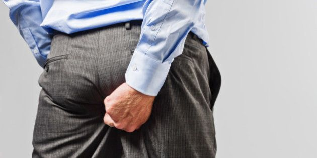 Rude businessman scratches his buttocks - NOT something to do in