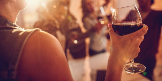 Close up of a businesswoman enjoying in a glass of red wine while being at office party with her