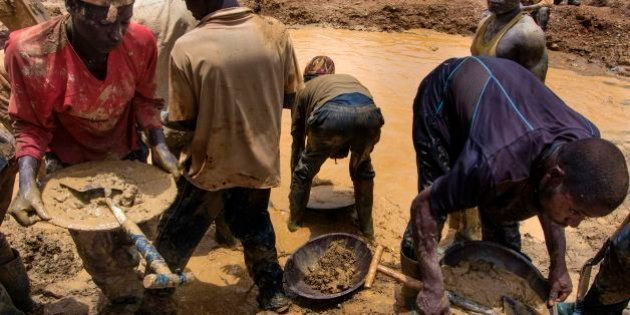 Galamseyers, illegal miners from Niger, work beside a pond close to Kibi town on April 10, 2017. Immigrants...
