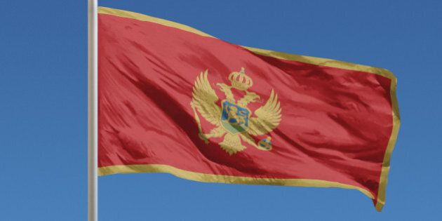 Flag of Montenegro in front of a clear blue