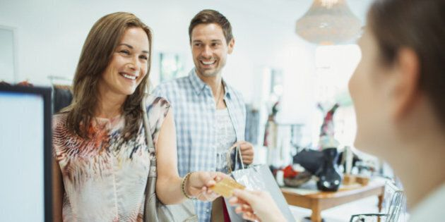 Couple paying with credit card in clothing store