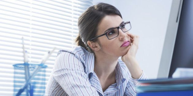 Bored office worker at desk staring at computer screen with hand on