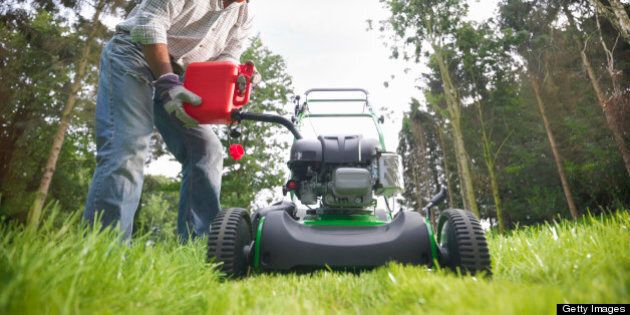 Man pouring gas into lawn mower