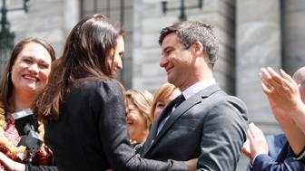 FILE - In this Oct. 26, 2017, file photo, New Zealand Prime Minister Jacinda Ardern, center left, embraces her partner Clarke Gayford after speaking to well-wishers in front of the parliament in Wellington, New Zealand. A spokesman for Ardern said on Friday the pair got engaged over the Easter break in the town of Mahia but said any further details would be for Ardern to discuss when she next speaks to media on Monday. (AP Photo/Nick Perry, File)