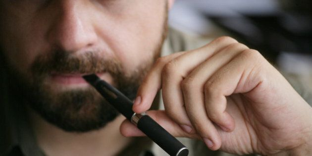 Close up view on the mouth of a bearded man holding and smoking an electronic