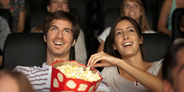 Couple eating popcorn in movie
