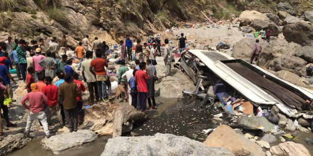 Indian rescue personnel and volunteers stand amidst wreckage and victims after a bus accident, at the bottom of a ravine near the River Tons at Chopal, some 115kms north of Shimla on April 19, 2017. A bus has swerved off a mountain road and plunged into a deep ravine in a Himalayan region of northern India, killing at least 44 people, an official said. The bus with 56 passengers on board plunged into a river in northern Himachal Pradesh state. / AFP PHOTO / STR (Photo credit should read STR/AFP/Getty Images)