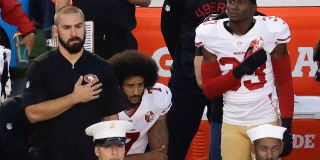 San Francisco 49ers quarterback Colin Kaepernick, middle, kneels during the national anthem before the...