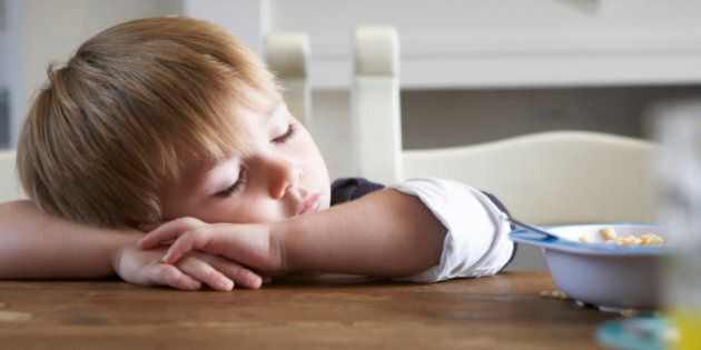 boy asleep on the kitchen table at breakfast time