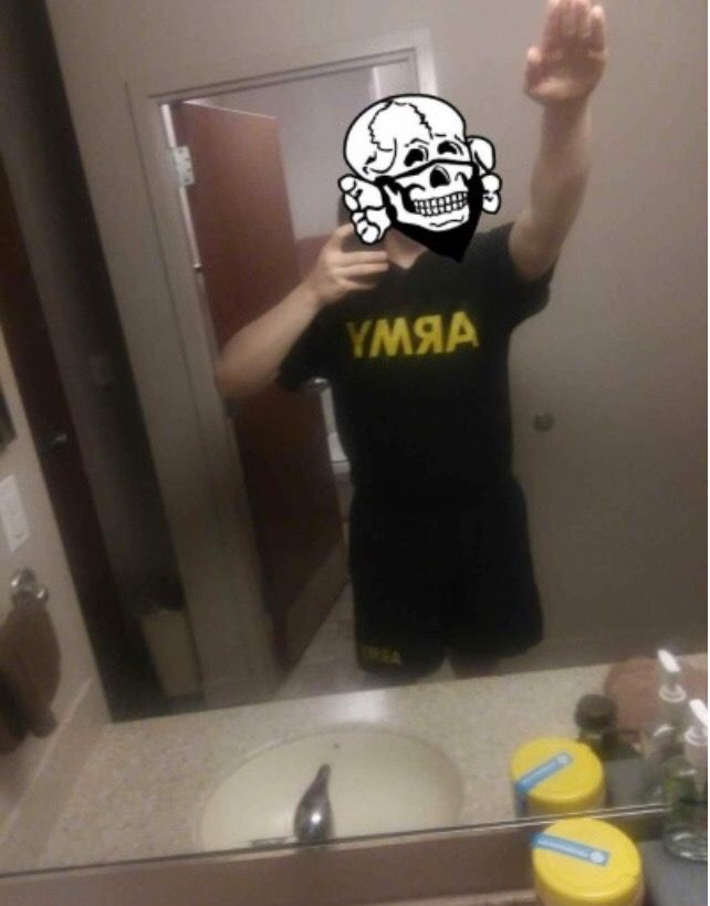 A photo posted to Corwyn Carver's Tumblr page, showing him in Army shorts and and an Army t-shirt, throwing up a Nazi salute. His face is blocked out by a skull-and-bones illustration often used by members of the Atomwaffen Division, a neo-Nazi group.