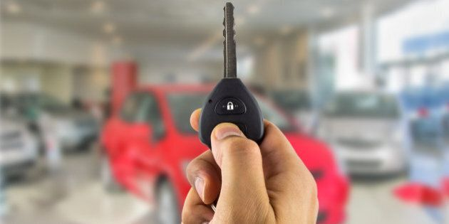 man holding a car key with remote in the concessionaire