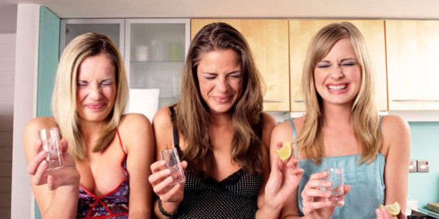 Three Teenage Girls Sit at a Kitchen Counter Grimacing After Drinking a Shot of