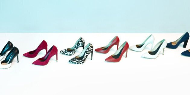 A line of pairs of women's high heeled shoes. Studio