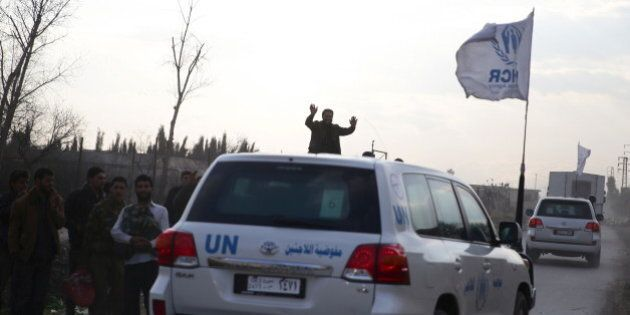 Men gesture as they welcome an aid convoy of Syrian Arab Red Crescent and UN driving through the rebel...
