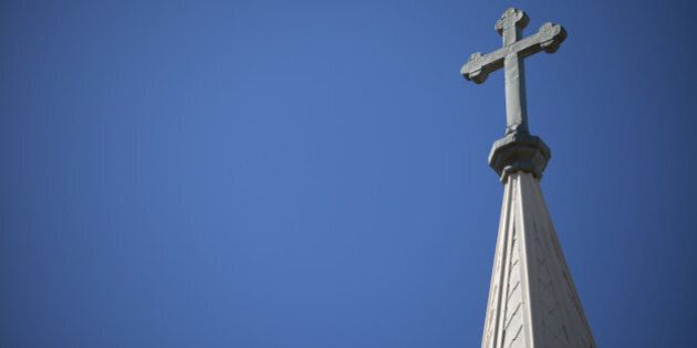 A Crucifix rises high above the skyline on top of a church's