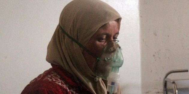 A woman, affected by what activists say was a gas attack, breathes through an oxygen mask inside a field...