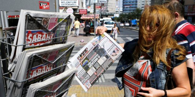 A woman buy a newspaper from a kiosk in Istanbul, Thursday, July 28, 2016. Authorities issued warrants...