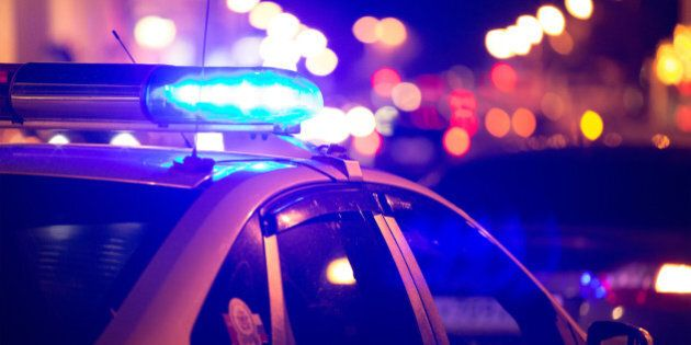 Blue light flasher atop of a police car. City lights on the