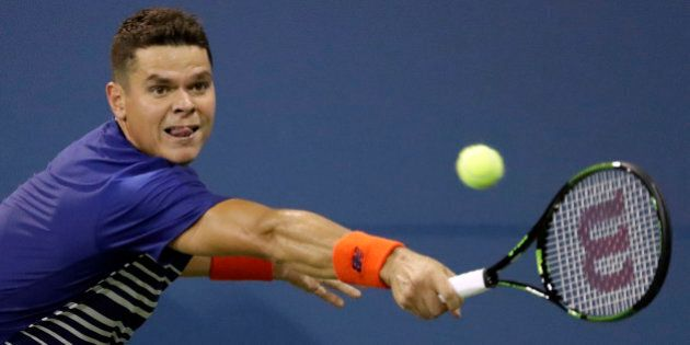 Milos Raonic, of Canada, returns a shot to Dustin Brown, of Germany, during the first round of the US...