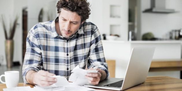 Serious mid adult man reading bills while making online payment at