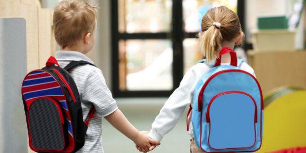 Two cute little children walking to school - Rear