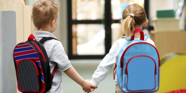 Two cute little children walking to school - Rear view