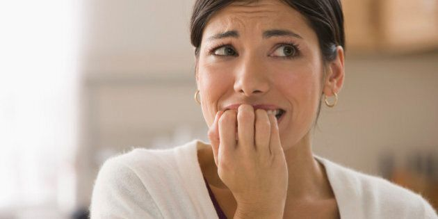 Afraid mixed race woman biting fingers