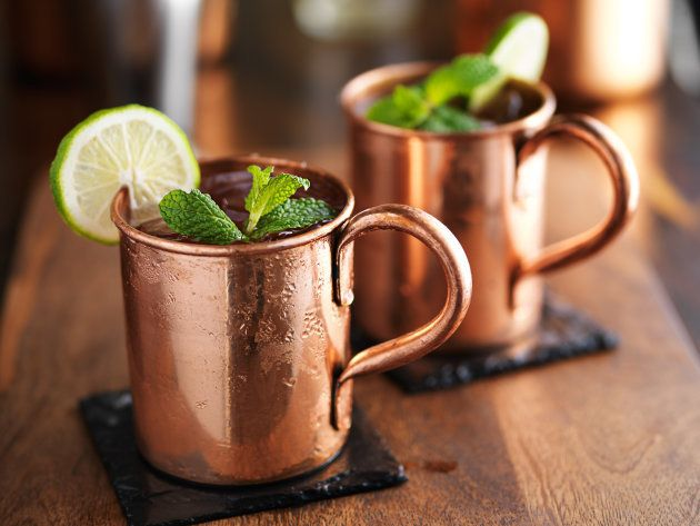 moscow mules in copper cups on slate coasters, garnished with mint and