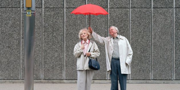 Senior man holding red umbrella over woman, standing on
