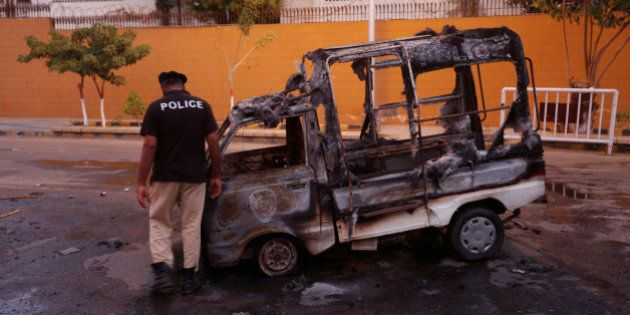 A policeman inspects a vehicle burned by Mutahida Qaumi Movement (MQM) political party protesters, in...
