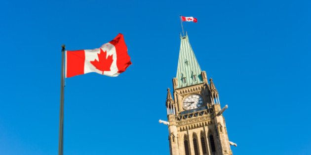 Close up of peace tower (parliament building) with a big canadian flag over blue sky in Ottawa,