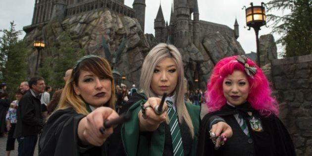 Fans pose in front of Hogwarts castle at the Grand Opening of the 'Wizarding World of Harry Potter' to...