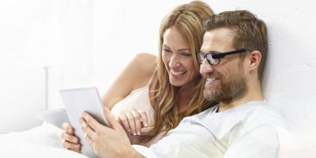 Young woman with man wearing smart glasses using digital tablet on