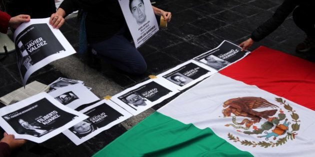 People place photos of murdered journalists next to the national Mexican flag during a demonstration...