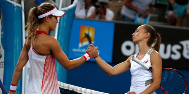 Eugenie Bouchard of Canada is congratulated by Aleksandra Krunic of Serbia during their first round match...
