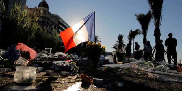 A French flag stands stall amongst a floral tribute for the victims killed during a deadly attack, on...