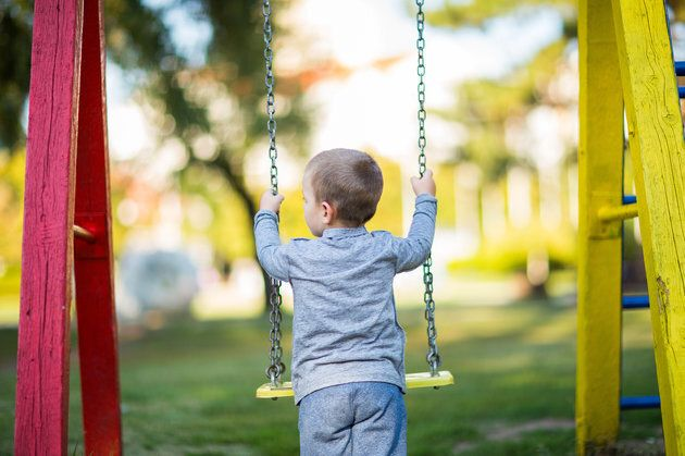 Blond boy swinging on the playground,rear