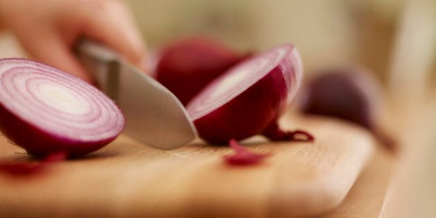 Knife chopping red onion on cutting board
