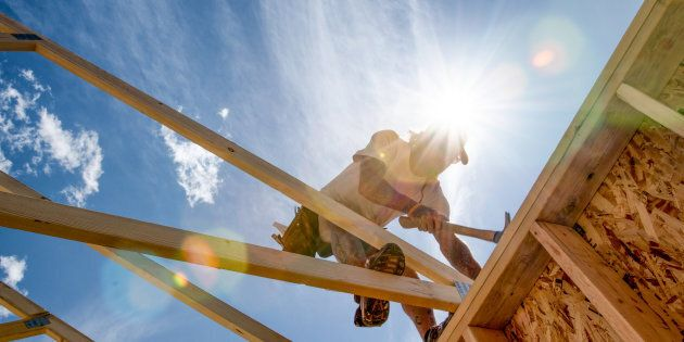 Manual laborer poised on a new construction hammering a piece of frame work with The sun and a partly...