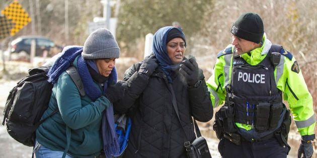 Un officier de la GRC parle avec des femmes originaires du Soudan après qu'elles aient traversé la frontière canado-américaine de manière irrégulière près de Hemmingford, au Québec, le 26 février 2017. (GEOFF ROBINS/AFP/Getty Images)